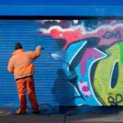 Man verwijdert anti graffiti coating van metaal